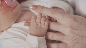 De pasgeboren hand van de holdingsmoeder ` s sluit omhoog in langzame motie Het concept van de familie stock video