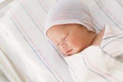De pasgeboren jongen die van de zuigelingsbaby in een het ziekenhuisbed ligt stock foto's