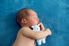 De pasgeboren leugens met het blauwe zachte stuk speelgoed dragen op het bed Royalty-vrije Stock Afbeelding