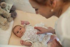 De pasgeboren leuke baby ligt in de voederbak en het kijken moeder royalty-vrije stock foto's