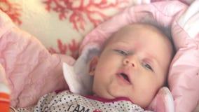 De pasgeboren mooie baby ligt op zijn rug en probeert voor het eerst te glimlachen 1920x1080 stock videobeelden