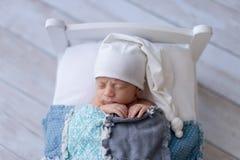 De pasgeboren Slaap van de Babyjongen op een Uiterst klein Bed stock afbeelding