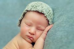 De pasgeboren slaap van de babyjongen in de foetale positie inzake een blauwe backgr Royalty-vrije Stock Fotografie