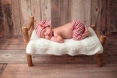 De pasgeboren Slaap van de Babyjongen op een Uiterst klein Bed Royalty-vrije Stock Fotografie