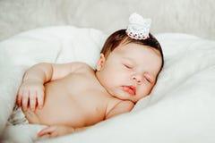 De pasgeboren slaap van het babymeisje die in witte deken wordt verpakt Stock Afbeelding