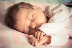 De pasgeboren slaap van het babymeisje op zachte deken met natuurlijk licht Royalty-vrije Stock Foto