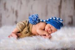 De pasgeboren slaap van het jongensjonge geitje in blauwe hoed Stock Afbeeldingen
