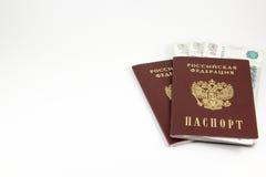 De paspoorten van de Russische Federatie en het geld op witte bac Stock Foto's