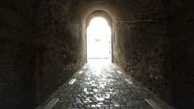 De passage aan wit licht binnen de oude muren van de baksteengang stock videobeelden