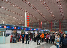 De passagiers bevinden zich in rijen in tellers bij airpo van Peking te controleren Stock Foto's