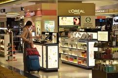 De passagiers doen sommigen die vóór start in Changi Luchthaven winkelen Royalty-vrije Stock Afbeeldingen