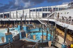 De passagiers genieten op zee van een dag op het hoogste dek van cruiseschip Stock Afbeeldingen