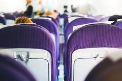 De passagiers zitten in de blauwe leunstoelen van de vliegtuigen tijdens de vlucht, de mening van de rug van toeristen het vliege royalty-vrije stock foto