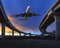 De passagiersjet die over de brug van het vervoerland vliegen gebruikt dit beeld voor lucht en landvervoersthema Stock Fotografie