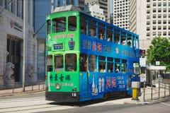 De passen van de dubbeldekkertram door de straat in Hong Kong, China stock foto's
