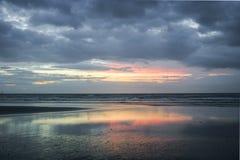 De pastelkleur kleurde zonsondergang bij het Nederlandse strand met bezinningen in een pool van water royalty-vrije stock foto's