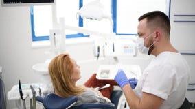 De patiënt bij tandartskabinet maakt tot mondelinge hygiëne tandbehandeling tijdens chirurgie stock videobeelden