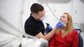 De patiënt bij tandartskabinet maakt tot mondelinge hygiëne tandbehandeling tijdens chirurgie stock footage