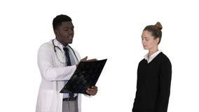 De patiënt komt aan arts met x ray Fysiotherapeut die röntgenstraal verklaren aan patiënt op witte achtergrond stock videobeelden