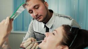 De patiënt onderzoekt het tandartswerk aangaande haar tanden zittend als speciale voorzitter stock video