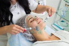 De patiënt ontvangt procedure Darsonvald Zijn gezicht is gesmeerd met gel stock fotografie