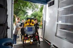 De Patiënt van de lading in Ziekenwagen stock afbeeldingen