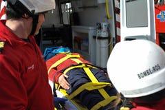 De patiënt van het brandbestrijdersvervoer op ziekenwagen royalty-vrije stock afbeelding