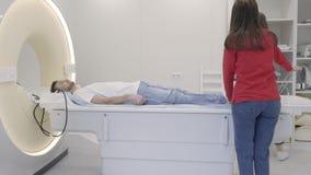 De patiënt van de verpleegstersvoorbereiding voor magnetic resonance imagingsonderzoek stock footage