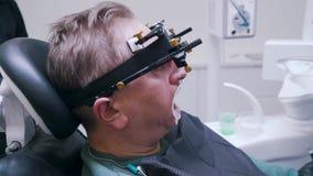 De patiënt wordt bevestigd de kaak en doet chirurgie in de tandkliniek stock footage