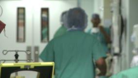 De patiënt wordt genomen aan chirurgie aangezien het personeel gang vult stock footage