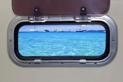 De patrijspoort turkooise tropische blauwe oceaanoverzees van de boot stock foto's