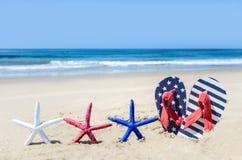 De patriottische achtergrond van de V.S. met zeester op het zandige strand Stock Afbeelding