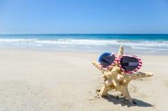 De patriottische achtergrond van de V.S. met zeester op het zandige strand Stock Foto