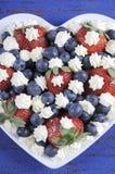 De patriottische rode, witte en blauwe bessen met verse slagroom speelt - verticale dichte omhooggaand mee Royalty-vrije Stock Foto