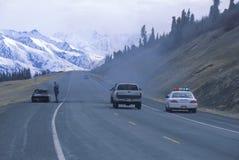 De patrouillerend politieagent en de auto van de weg op brand Royalty-vrije Stock Fotografie