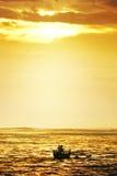 De peddelboot van de visser in zonsondergang Stock Fotografie