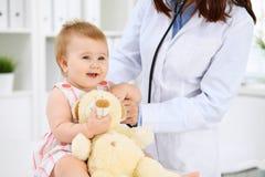 De pediater behandelt baby in het ziekenhuis Het meisje is onderzoekend door arts met stethoscoop Vertragingen en wapens Stock Fotografie