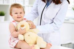 De pediater behandelt baby in het ziekenhuis Het meisje is onderzoekend door arts met stethoscoop Vertragingen en wapens stock foto's