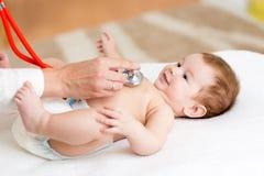 De pediater onderzoekt drie van de babymaanden jongen stock foto