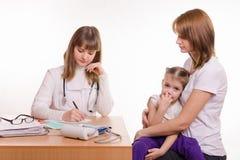 De pediater schrijft benoeming voor behandelings ziek kind stock foto's