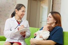 De pediater van schrijft aan pasgeboren baby het medicijn voor Royalty-vrije Stock Foto's