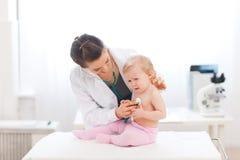 De pediatrische arts onderzoekt schreeuwende baby Royalty-vrije Stock Fotografie