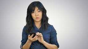 De peinzende Aziatische presentatie van de onderneemsterlezing op smartphone, die camera op witte achtergrond bekijken royalty-vrije stock fotografie
