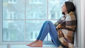 De peinzende blootvoetse vrouw krimpt van koude en bundel op verwarmingstoestel op plaid stock video