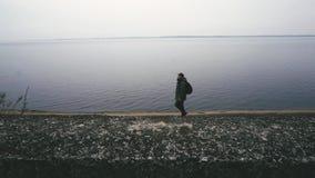 De peinzende en geconcentreerde mens loopt langs overzees Hij kijkt in camera vooruit en, koude dalingsweer en zonsondergang stock videobeelden