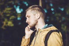De peinzende gebaarde mens die op smartphone spreekt en luistert aandachtig Jong toevallig Europees mannetje in gele jasjes, vraa Royalty-vrije Stock Fotografie