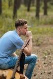 De peinzende gitarist creeert aard wandelingsconcept stock foto's