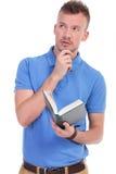 De peinzende jonge toevallige mens houdt boek Royalty-vrije Stock Fotografie