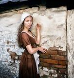 De peinzende jonge vrouw in een rustieke kleding die zich dichtbij oude bakstenen muur in oud huis bevinden voelt eenzaam Cindere Stock Fotografie