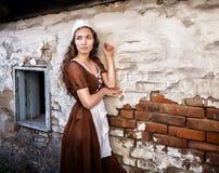 De peinzende jonge vrouw in een rustieke kleding die zich dichtbij oude bakstenen muur in oud huis bevinden voelt eenzaam Cindere Royalty-vrije Stock Fotografie